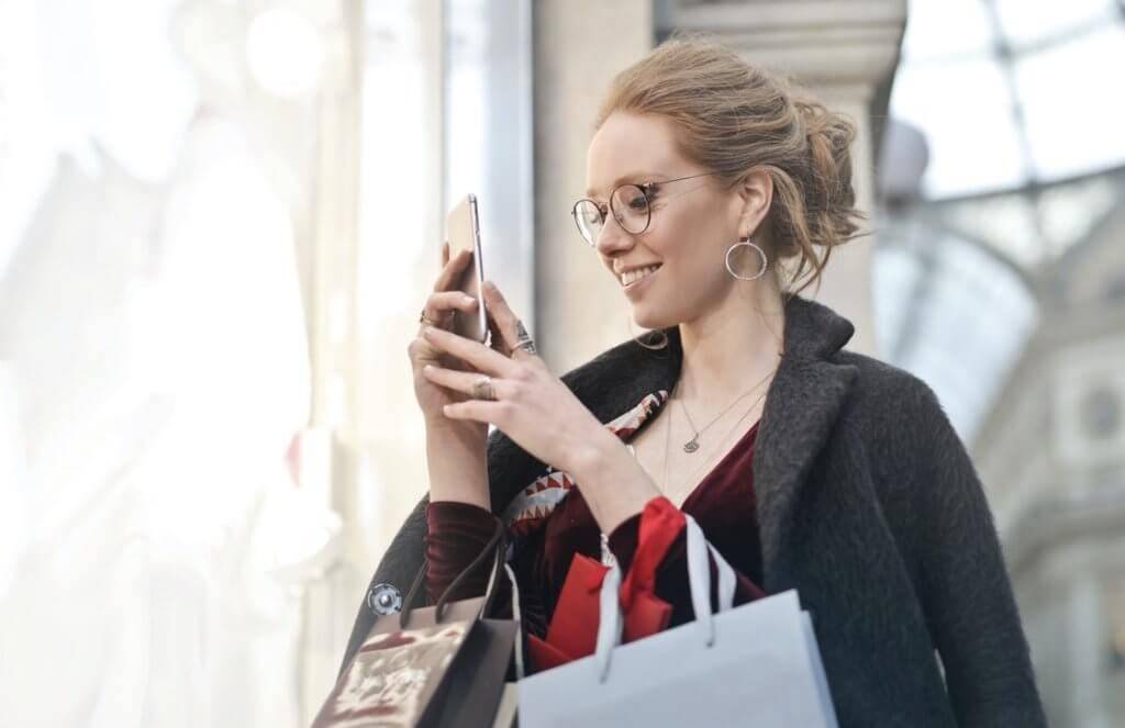 Woman using smartphone for social shopping.