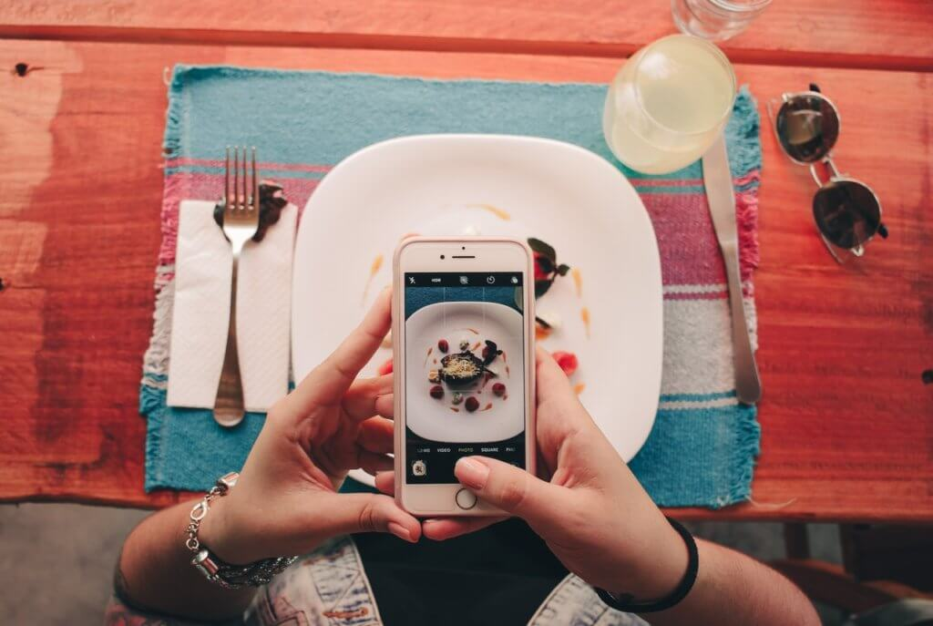 Woman taking picture of food from restaurant.