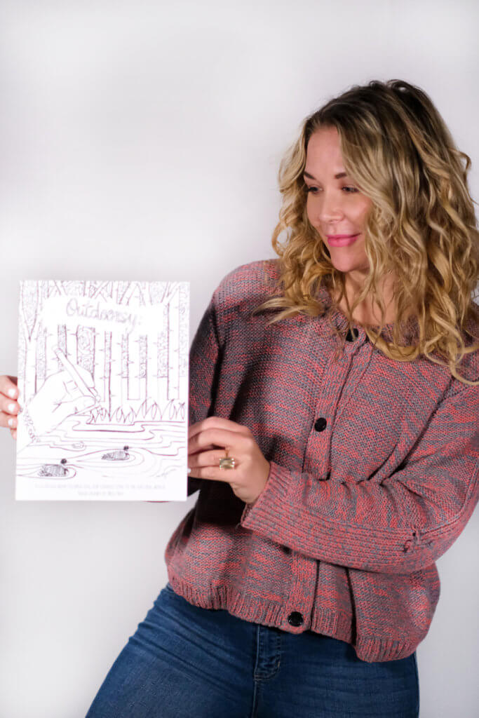 A woman holding a image from the Outdoorsy coloring book.