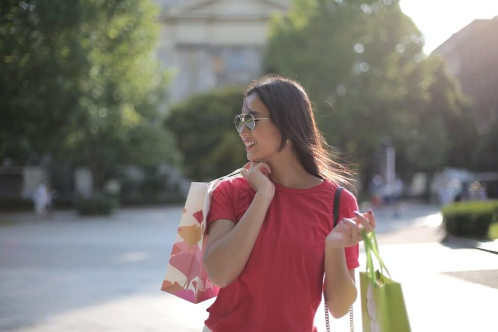 Young woman holding shopping bags after retail shopping.