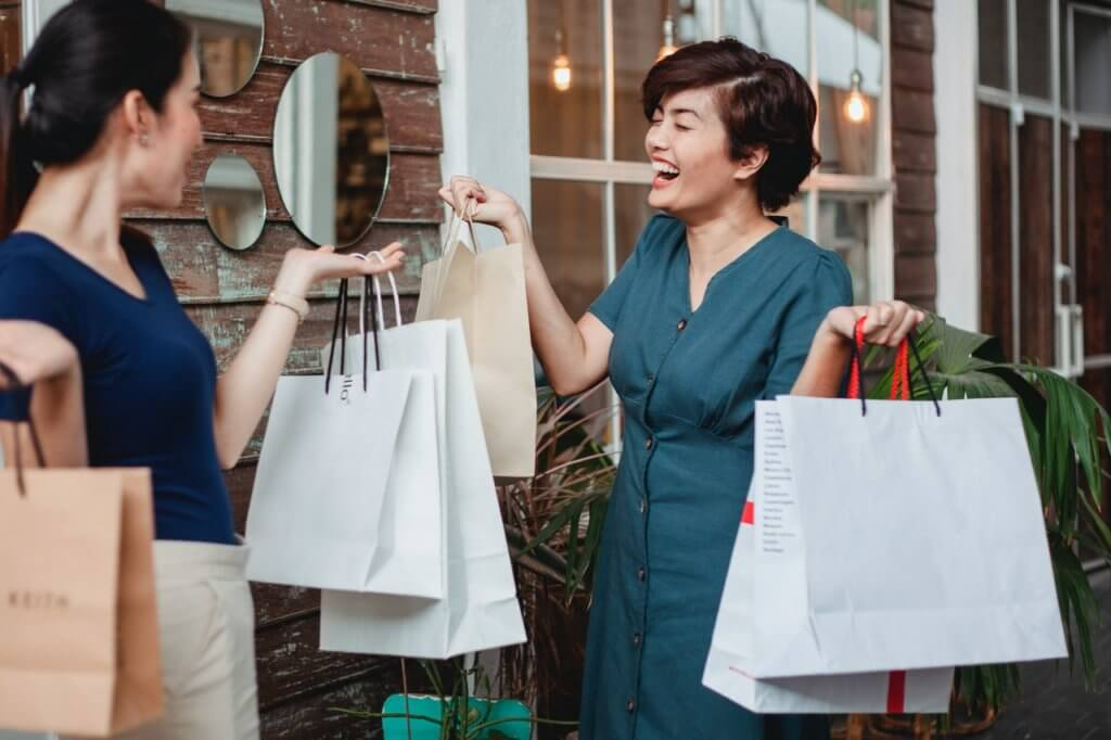Two women in shopping mall holding retail bags.