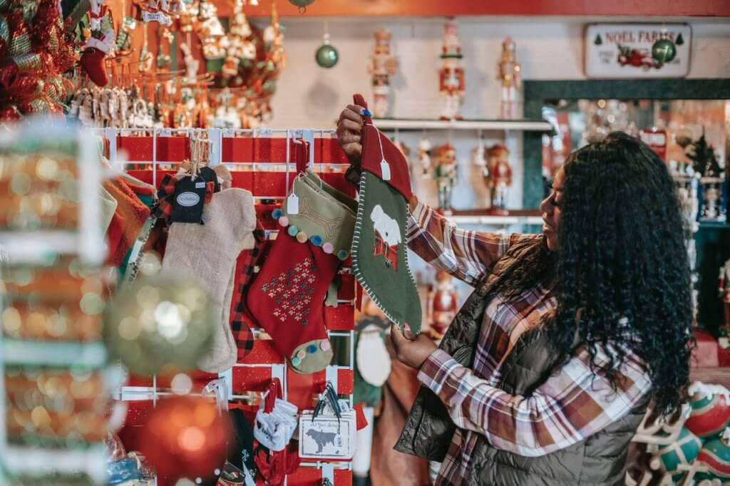 Woman looking at Christmas stocking and other decorations in store.
