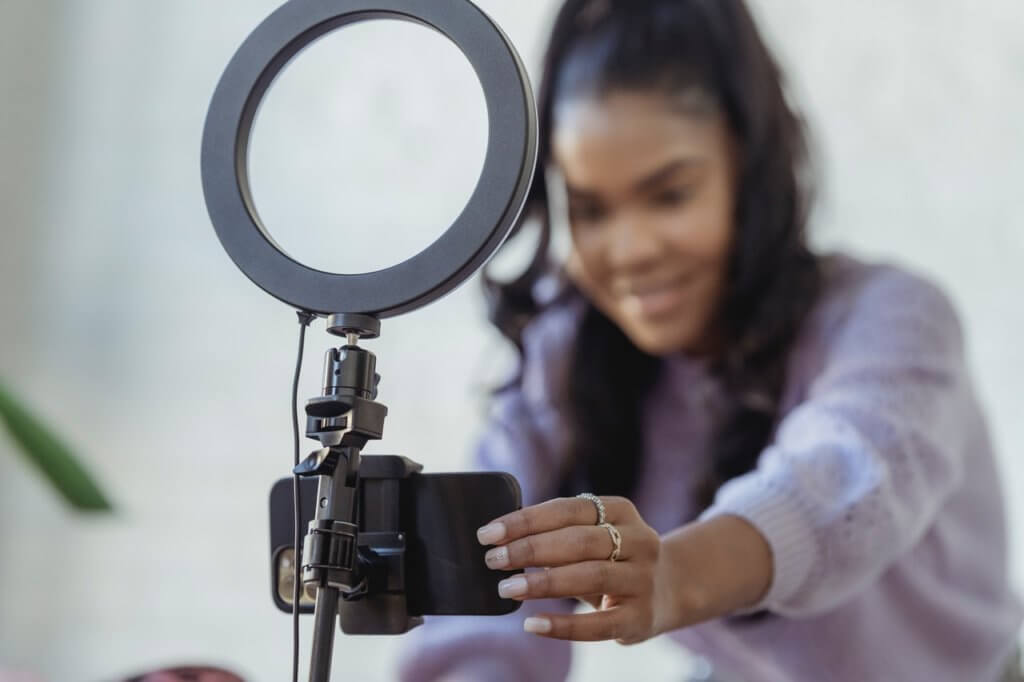 Young woman fixing camera for tutorial video.